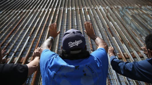 Immigrant advocacy members pray at the U.S.-Mexico border fence on May 1, 2016, in Tijuana.